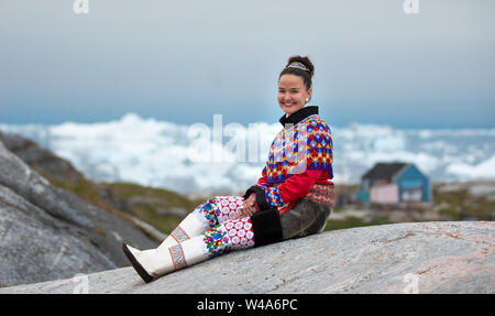 Young inuit woman in traditional clothing posing for photos in a small Greenlandish village. - Stock Photo