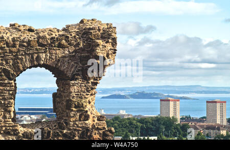 St Anthony's Chapel's ruins in Holyrood Park in the foreground and a panomara of the Edinburgh and Inchkeith Island in the background - Stock Photo