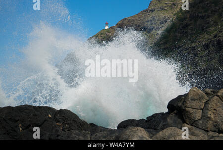 View of a crashing wave against a rocky shore with the Mokapu lighthouse in the background. This is on Oahu, Hawaii's south shore. - Stock Photo