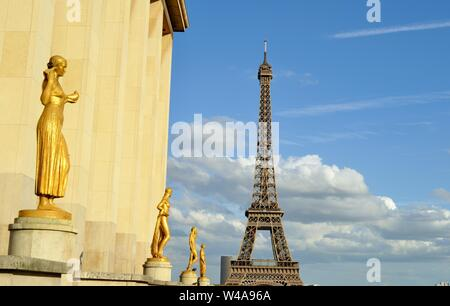 Beautiful golden statues at the Trocadero terrace in Paris with the Eiffel Tower with the blue sky and the white clouds background. - Stock Photo
