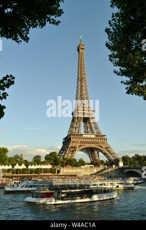 Paris/France - August 18, 2014: Beautiful panoramic view to the Eiffel Tower and river Seine intense cruise passenger ships traffic in a sunny day. - Stock Photo