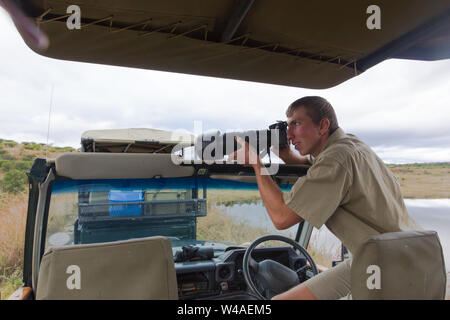 male game ranger using a professional camera and taking a photo of African wildlife while sitting on the door of the safari 4x4 game drive vehicle - Stock Photo