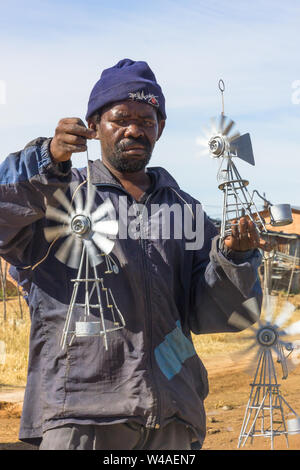 Black African poor street vendor selling hand made metal wind pumps on the side of the road to make some money to ease poverty in South Africa - Stock Photo