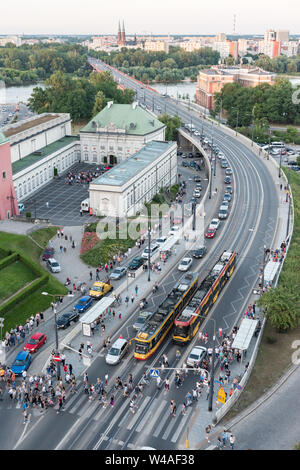 Queues of cars form as more than a hundred people exit trams and cross the road at the Stare Miasto tram stop near Castle Square in Warsaw's Old Town. - Stock Photo