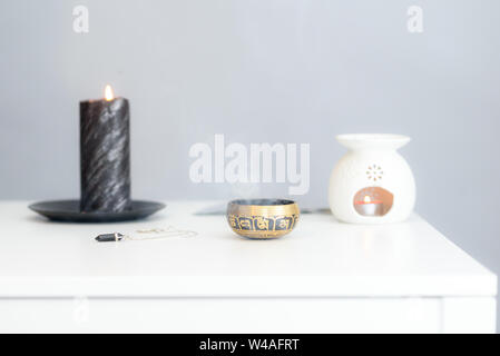 Cozy home interior decor, burning candles. Burning candles on wooden white table against grey wall. Space for text. Soft focus. - Stock Photo
