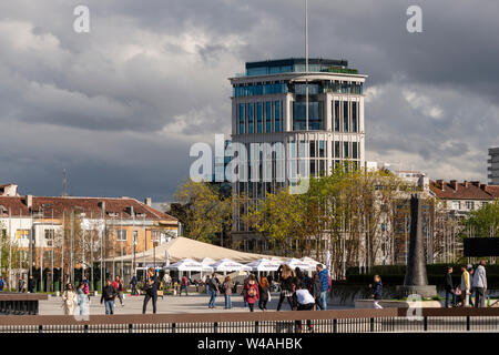 Sofia Bulgaria urban scene of people enjoying the late afternoon in downtown Sofia with The Needle office building against cloudy sky in background - Stock Photo