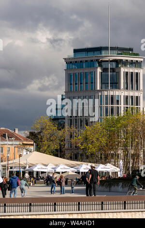 Sofia Bulgaria urban scene of people enjoying the late afternoon in downtown Sofia with The Needle office building against cloudy sky as background. - Stock Photo
