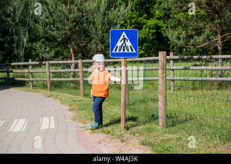 Small boy on road. The concept of studying the rules of the road. - Stock Photo