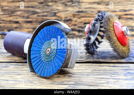 Angle grinder with grinding disc brushes and abrasive wire brushes lies on the background of a wooden table. - Stock Photo