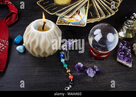 Still life with the tarot cards, magic stones and candles on wooden table. Fortune telling seance or magic ritual.