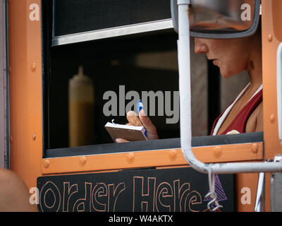 Food trucks gather for a festival in Sanford, Florida. Cashier takes order from orange truck. - Stock Photo