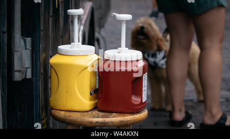 Ketchup and mustard outside a food truck at a dog friendly festival open market in Florida. - Stock Photo
