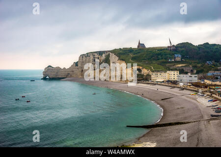 Scenic landscape of Etretat, beach, waterfront and Falaise d'Amont, iconic cliff of Normandy Coast, at dusk, France. - Stock Photo