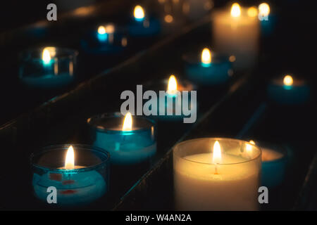 Closeup of rows of prayer candles burning in blue glass tealights in a church. Shallow depth of field. - Stock Photo