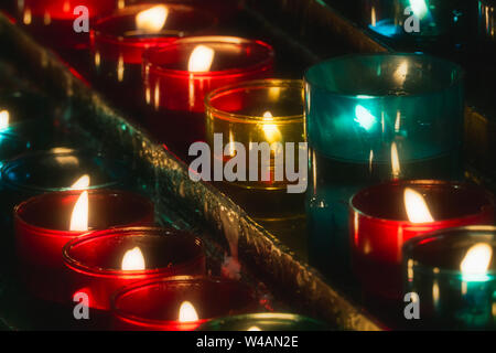 Closeup of rows of candles burning in multicolored glass tealights in a church. - Stock Photo