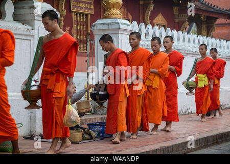 People giving alms to young Buddhist monks on the street early in the morning in front of the Wat Sensoukaram Temple in Luang Prabang, Laos. Tak Bat. - Stock Photo