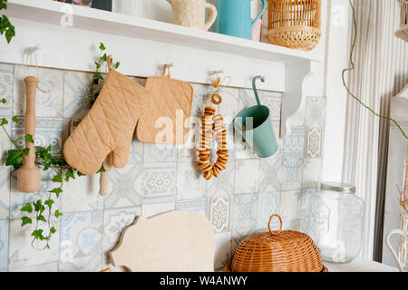 Kitchen towel and glove on work top in modern kitchen, kitchen accessories hanging in the roof rail on the white wall. - Stock Photo