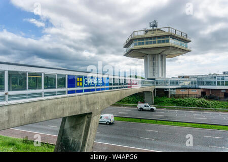 Brutalist architecture of the all weather enclosed bridge across the M6 motorway and the Pennine Tower of Lancaster Forton Services opened in 1965. - Stock Photo