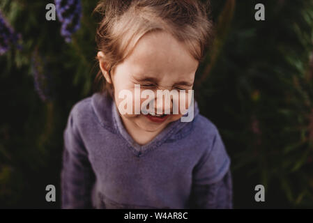 Close up portrait of little toddler girl scrunching nose and laughing