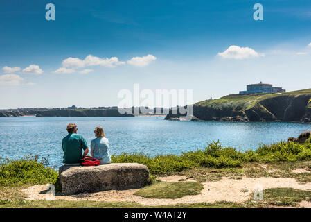 Holidaymakers sitting on a rock on Towan Head Headland overlooking Newquay Bay in Cornwall. - Stock Photo