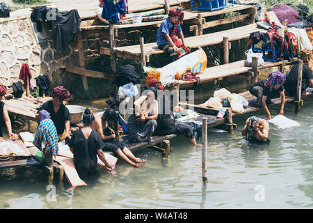 Indein, Myanmar - March 2019: Burmese women from PaO dragon people tribe washing clothes in the river close to Inle lake. - Stock Photo