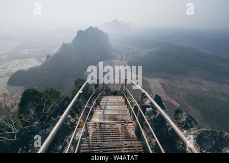 Mountain peak with empty stairs going down during sunrise foggy morning in Hpa-An, Myanmar. - Stock Photo