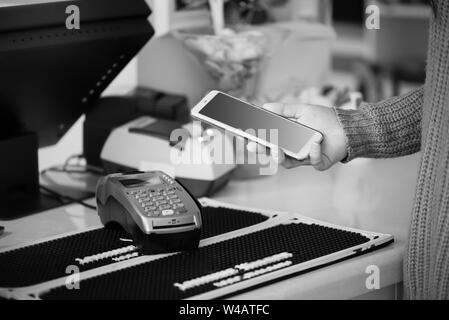 Shopper does payment using smartphone. NFC technology in people life - Stock Photo