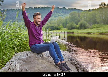 A bearded young man sits on a rock near the river with a laptop in his lap and rejoices with his hands raised to the top. - Stock Photo