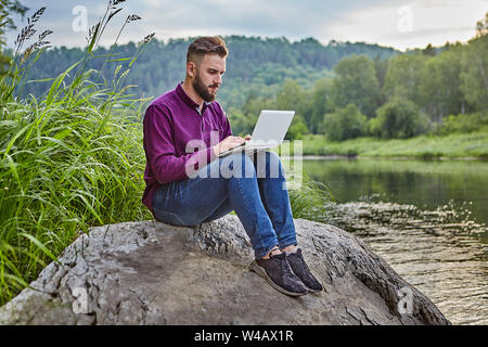 A young bearded man sits on a stone near the river with a laptop in his lap, he looks at the screen and types text on the keyboard. - Stock Photo
