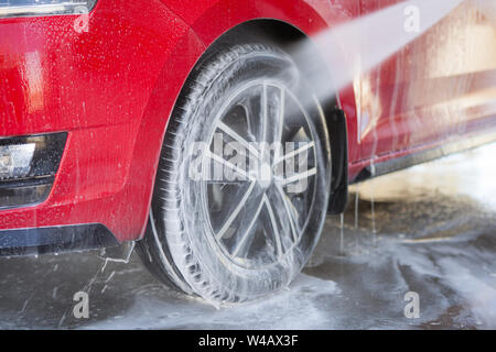 Car cleaning. Wash red car with soap. High pressure water washing - Stock Photo