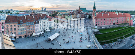 Panoramic view of Castle Square in Warsaw, Poland, as the sun begins to set over the Old Town with people outside Sigismund's Column and Royal Castle.
