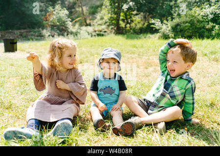 Straight on portrait of three kids playing and laughing together