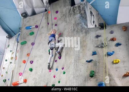 young girl climbing rock wall at indoor rock  climbing gym - Stock Photo
