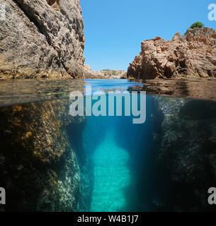 Narrow passage between rocks on the seashore, split view over and under water, Mediterranean sea, Spain, Costa Brava, Palafrugell, Catalonia - Stock Photo