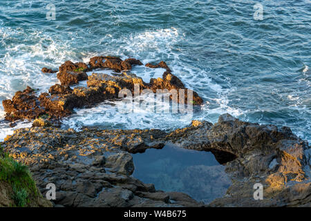 Waves splashing against rocks at low tide form a tide pool in Laguna Beach. Tide pools are habitats of adaptable animals studied by marine biologists. - Stock Photo