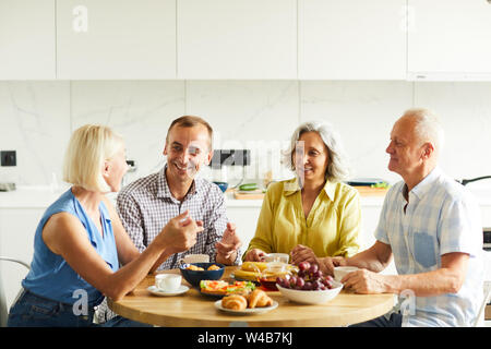 Group of cheerful senior people enjoying lunch while sitting around table in kitchen, copy space - Stock Photo