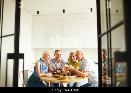 Group of cheerful senior people sitting around table in kitchen shot through open doors, copy space - Stock Photo