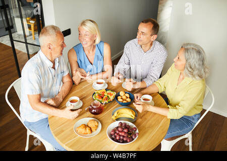High angle view at group of cheerful senior people enjoying lunch while sitting around table in kitchen, copy space - Stock Photo