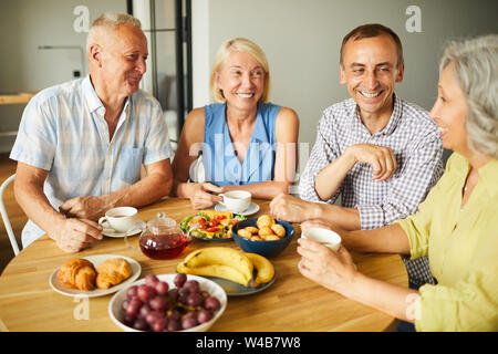 Group of mature people chatting cheerfully while sitting around table in kitchen, copy space - Stock Photo