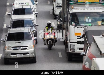 Bangkok, Thailand - May 28, 2018: Police motorbike manouvering through a traffic jam on Kanchana Phisek Road, the ring road around Bangkok, at Talat B - Stock Photo