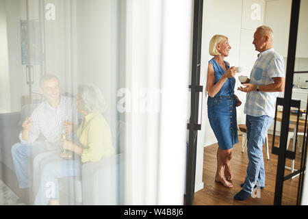 Full length portrait of elegant mature couple chatting during party shot through open door, copy space - Stock Photo