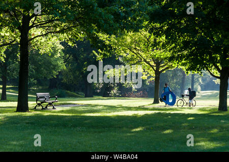 A young man with camping gear and a young woman with a bike in a park early in the morning, Canada. Ideal setting for meditation, jogging or a picnic. - Stock Photo
