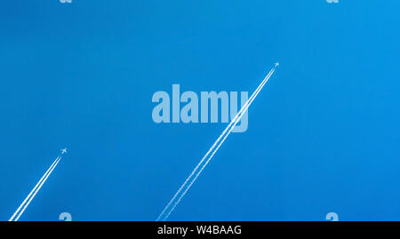 Airplane with white condensation tracks. Jet plane on clear blue sky with vapor trail. Travel by airplane concept. Trails of exhaust gas from airplane - Stock Photo