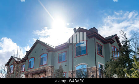 Panorama frame Facade of a home surrounded with lush trees and snowy ground in winter. The sun is shining brightly against the blue sky with puffy clo - Stock Photo
