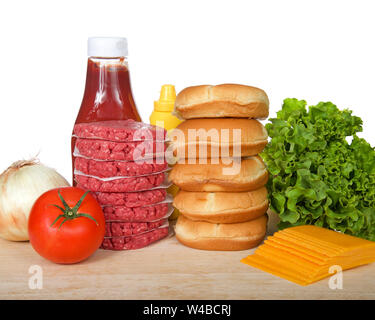 Raw hamburger patties stacked on wood table with buns, lettuce, cheese, tomato, onion, ketchup, mustard. Ingredients for a bbq lunch or dinner isolate - Stock Photo