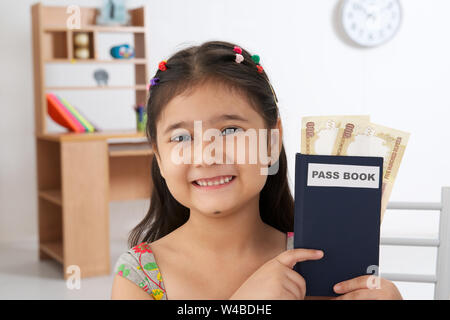 Indian girl showing bank book with banknotes and smiling at home - Stock Photo