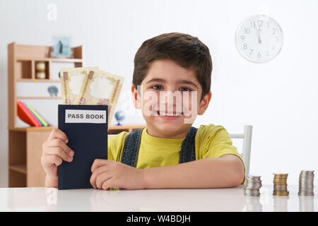 Indian boy showing bank book with banknotes and smiling at home - Stock Photo