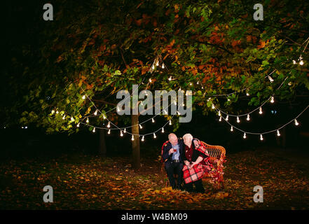 Happy senior couple drinking tea in the evening sitting on the couch - Stock Photo