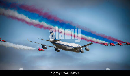 Flypast by the RAF Red Arrows aerobatic display team in formation with a BOAC liveried Boeing 747 at The Royal International Air Tattoo, Fairford, UK - Stock Photo