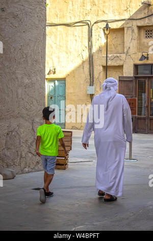 Dubai, UAE - December 1, 2018: An Arab with a child walking through the streets of the old city. - Stock Photo